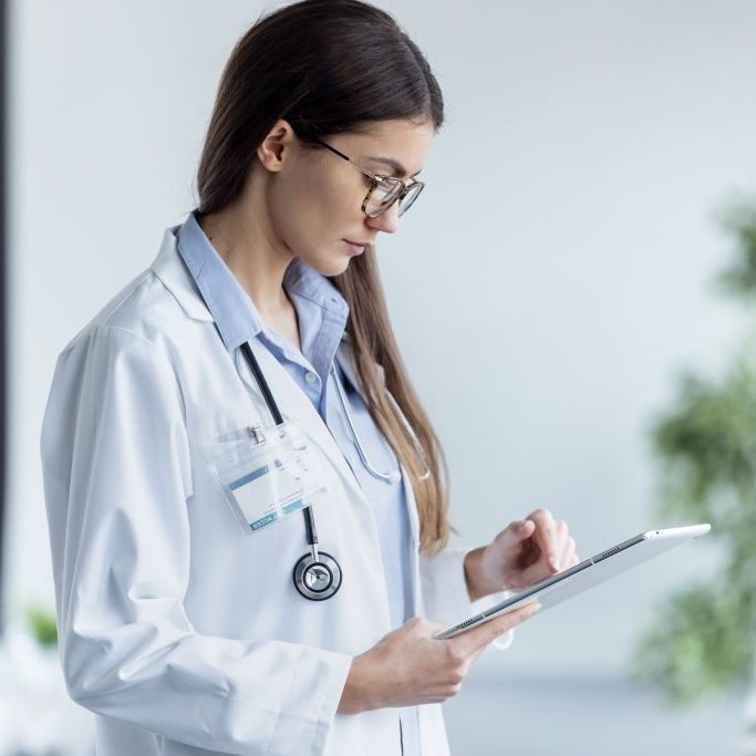female-doctor-using-her-digital-tablet-while-stand-3AFJ8BH-2-1024x683